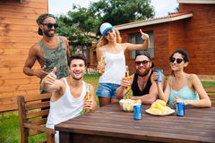 Cheerful young people drinking beer and showing thumbs up outdoors Stock Photography
