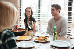 Cheerful young people enjoying meal while sitting at the dinning table Stock Photography