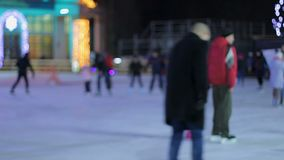 Cheerful young people and families skating on ice rink, active recreation