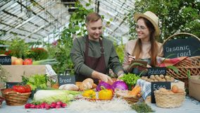 Cheerful young people farmers putting organic food on table at farm sales. Cheerful young people farmers are putting organic food on table at farm sales talking stock video