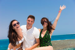 Cheerful young people having fun and standing on the yacht at a Stock Photos