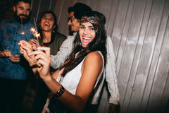 Cheerful young people having a party. Cheerful young people walking together at night and having fun. Multiracial group of friends hanging out in evening Royalty Free Stock Images