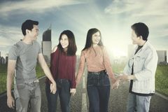 Cheerful young people hold hands on the road. Group of cheerful young people holding hands each other while standing on the road stock photos