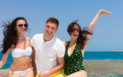 Cheerful young people laughing and standing on the yacht at a su Stock Image