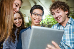 Cheerful young people laughing and using tablet Royalty Free Stock Photos