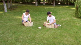 Friends play giant dominoes in the park in summer. stock video footage
