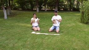 Cheerful teens playing dominoes in Park on grass. stock video footage