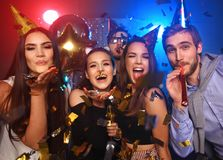Cheerful young people showered with confetti on a club party. Friends making big party in the night. Four people throwing confetti and drinking champagne stock photography