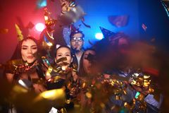 Cheerful young people showered with confetti on a club party. Friends making big party in the night. Four people throwing confetti and drinking champagne royalty free stock image