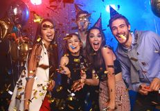 Cheerful young people showered with confetti on a club party. Friends making big party in the night. Four people throwing confetti and drinking champagne stock photo