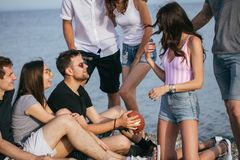 People spending nice time together while sitting on beach, having fun and drinking beer. Cheerful young people spending nice time together while sitting on beach stock image