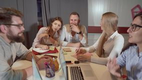 Men and women workers are making brainstorming in office room. Cheerful young people are talking joyfully during meeting in office. Men and women are stock video footage