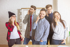 Cheerful young people on their phones. Group of beautiful cheerful young people in office talking on their phones all at once. Communication concept Royalty Free Stock Images