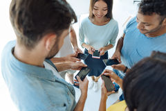 Cheerful young people using their smartphones Stock Images