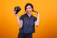 Cheerful young photographer with camera in her hand over yellow background in studio. Modern technology for photographers stock images