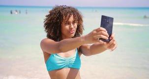 Cheerful ethnic woman taking selfie on beach stock video footage