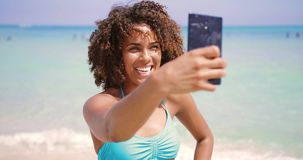 Cheerful ethnic woman taking selfie on beach. Cheerful young pretty ethnic woman standing on the beach and taking selfie with smartphone at seaside stock video footage