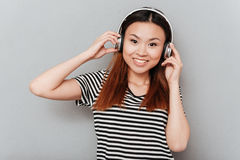 Cheerful young pretty woman listening music with headphones Stock Images