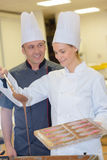 Cheerful young professionals pastry cooks preparing chocolate dessert Royalty Free Stock Image