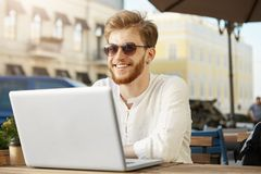 Cheerful young red haired male freelance designer in white shirt and sunglasses with earring smiles and working on Royalty Free Stock Photography