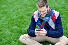 Cheerful young relaxed guy using mobile phone Stock Photography