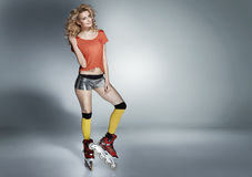 Cheerful young roller skater with curly hairstyle stock photos