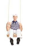 Cheerful young sailor swinging on a swing Stock Image