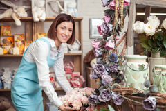Cheerful young saleswoman is working with flowers Stock Image