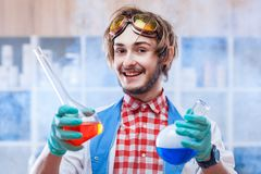 Cheerful man with chemistry flasks stock photos