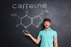 Cheerful young scientist showing chemical structure of caffeine molecule Royalty Free Stock Photos