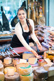 Cheerful young shopgirl selling cheese Stock Image