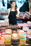 Cheerful young shopgirl selling cheese Stock Images