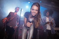 Cheerful young singer with musicians performing at nightclub. During music festival Royalty Free Stock Photo