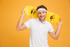 Cheerful young skater holding a skateboard over his shoulders. And looking at the camera isolated on orange background Stock Photography