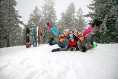 Cheerful skiers lying on snow and having fun Royalty Free Stock Image