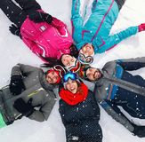 Cheerful skiers lying on snow and having fun top view Royalty Free Stock Images