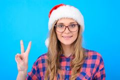 Cheerful young smiling lady in santa hat, checkered shirt and g royalty free stock photo