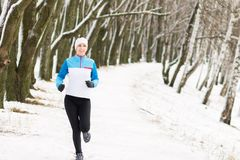 Cheerful young sport woman at winter outdoor activity. Smiling caucasian girl jogging in winter park stock image