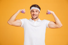 Cheerful young sportsman holding dumbbells and showing biceps Royalty Free Stock Image