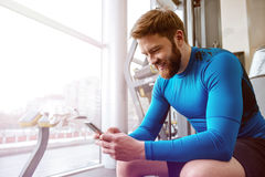 Cheerful young sportsman sitting in gym and looking at phone. stock photo