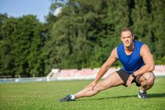 Cheerful young sportsman is stretching himself in. Handsome male runner is doing warm-up before training. He is looking forward with concentration. There is copy Royalty Free Stock Photography
