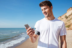 Cheerful young sportsman using smartphone on the beach Stock Images