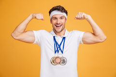 Cheerful young spotrsman with three medals showing biceps. Over yellow background royalty free stock images