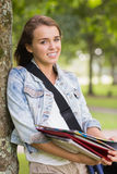 Cheerful young student leaning on tree holding her books Stock Photo