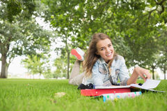 Cheerful young student studying on the grass Stock Photos