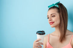 Cheerful young styled girl is enjoying hot drink Royalty Free Stock Images
