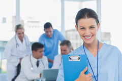 Cheerful young surgeon posing with colleagues in background. In medical office stock photos