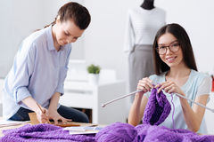 Cheerful young tailor enjoying her knitwork. Pleasant task. Beautiful slender women knitting a hat with purple threads while her colleague sitting on the table Stock Images