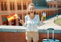 Traveller woman with trolley bag, Spain flag and green smoothie. Cheerful young traveller woman with trolley bag, Spain flag and green smoothie against Puerta De stock images