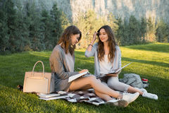 Cheerful young two women sitting outdoors in park writing notes. Picture of cheerful young two women sitting outdoors in park writing notes. Looking aside Stock Photo